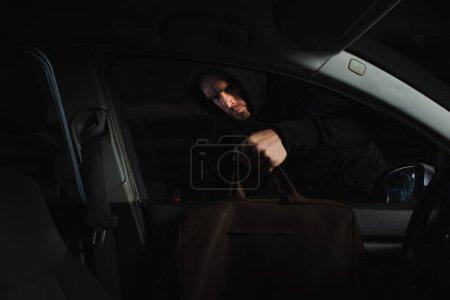 male robber in black hoodie stealing bag from car