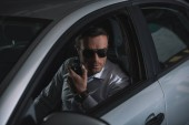 undercover male agent in sunglasses doing surveillance and using talkie walkie in car