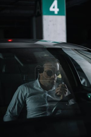 male undercover agent in sunglasses doing surveillance and using talkie walkie in car
