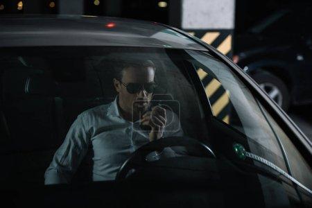 Photo pour Agent d'infiltration mâle à lunettes de soleil à l'aide de talkie walkie et assis dans la voiture - image libre de droit