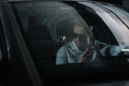 male undercover agent using talkie walkie and spying from car