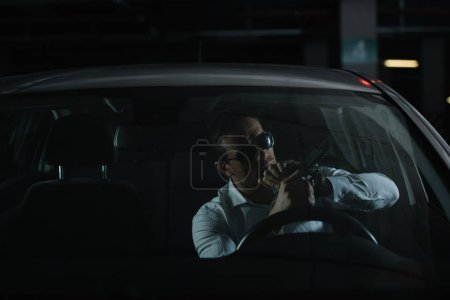serious male undercover agent in sunglasses charging gun in car