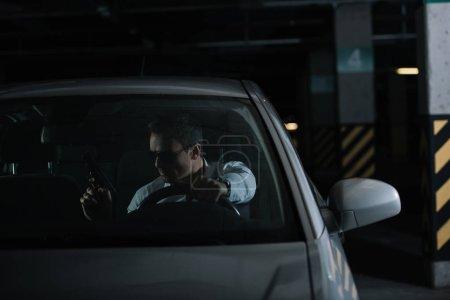 Photo pour Sérieux mâle détective privé en lunettes de soleil assis dans la voiture avec pistolet - image libre de droit
