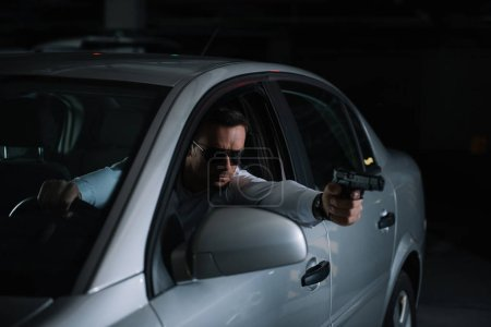 male private detective in sunglasses aiming by gun from car