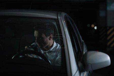 Photo pour Sérieux agent d'infiltration mâle faisant la surveillance par caméra dans sa voiture - image libre de droit