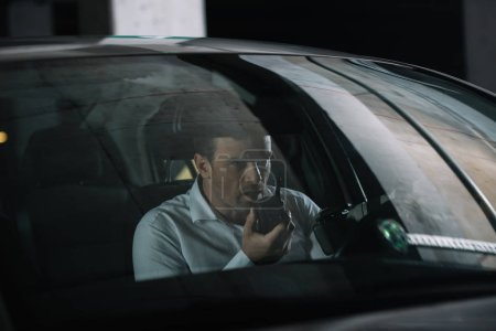 Photo for Undercover male agent doing surveillance and using talkie walkie in car - Royalty Free Image
