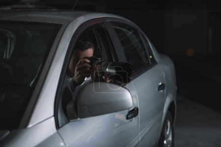 undercover male agent doing surveillance by camera from car