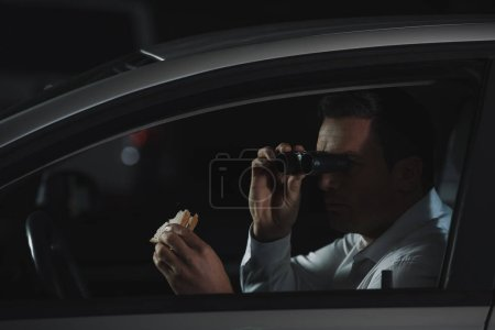 male private detective doing surveillance by binoculars and eating sandwich in car