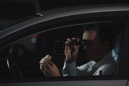 Photo pour Mâle détective privé faisant la surveillance de jumelles et mangé le sandwich en voiture - image libre de droit