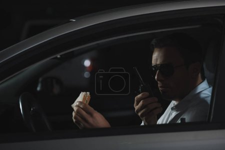 Photo for Male undercover agent in sunglasses having lunch and using talkie walkie in car - Royalty Free Image