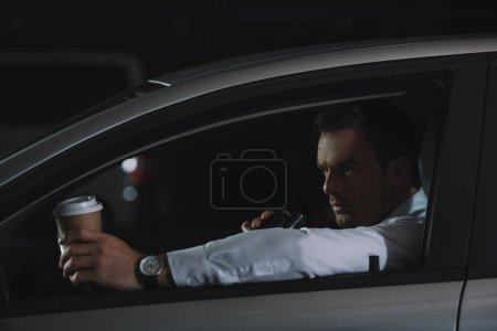 male undercover agent with paper cup of coffee using talkie walkie in car