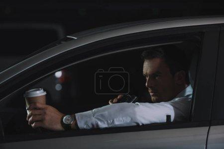 Photo pour Agent d'infiltration mâle avec une tasse de café à l'aide de talkie walkie en voiture en papier - image libre de droit