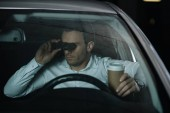 undercover male agent doing surveillance by binoculars and drinking coffee in car
