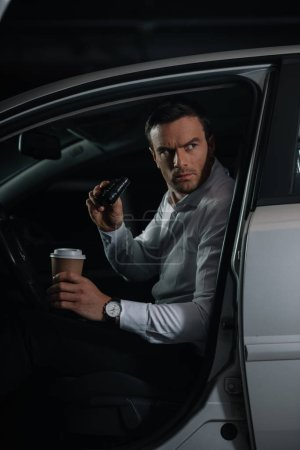 serious male undercover agent doing surveillance by binoculars and holding paper cup of coffee