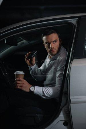Photo pour Agent d'infiltration mâle grave faisant la surveillance de jumelles et tenant la tasse de café en papier - image libre de droit