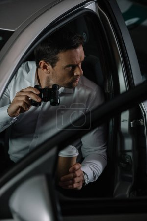 high angle view of undercover male agent with coffee cup doing surveillance by binoculars from car