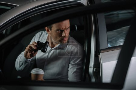 Photo for Concentrated undercover male agent doing surveillance by binoculars and drinking coffee in ca - Royalty Free Image