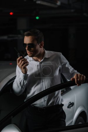 serious male undercover agent in sunglasses using talkie walkie near car