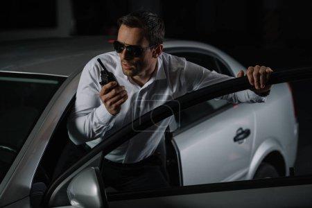 Photo pour Agent d'infiltration mâle sérieux dans lunettes de soleil à l'aide de talkie walkie près de voiture - image libre de droit