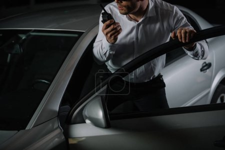 Photo pour Cropped image de mâle agent d'infiltration à l'aide de talkie walkie près de voiture - image libre de droit