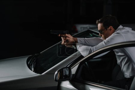 side view of undercover male agent in sunglasses aiming by gun