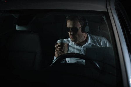 male private detective in headphones doing surveillance with laptop and drinking coffee in car