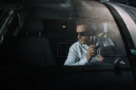 Photo pour Sérieux mâle détective privé dans les écouteurs faisant la surveillance par caméra avec objet verre de voiture - image libre de droit