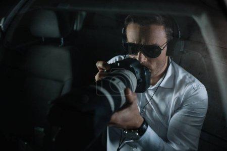 Photo pour Mâle détective privé dans les écouteurs faisant la surveillance par caméra avec objet verre de voiture - image libre de droit