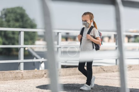 kid in protective mask walking with school bag on bridge, air pollution concept