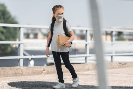 kid in protective mask walking with book on bridge, air pollution concept