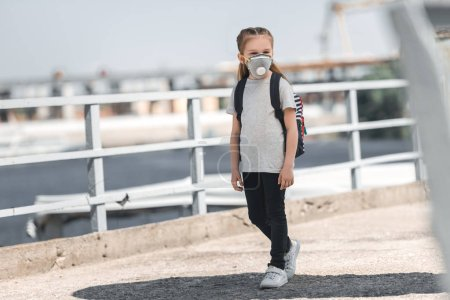 child in protective mask walking on bridge, air pollution concept