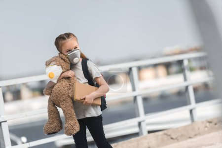child in protective mask walking with teddy bear and book on bridge, air pollution concept