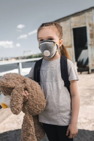 child in protective mask holding teddy bear on bridge, air pollution concept