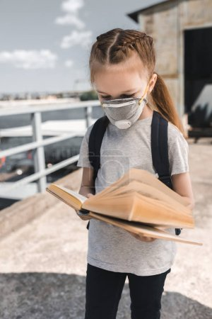 child in protective mask reading book on bridge, air pollution concept