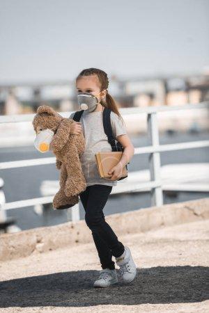 Photo pour Enfant au masque de protection tenant l'ours en peluche et livre sur le pont, la notion de pollution aérienne - image libre de droit