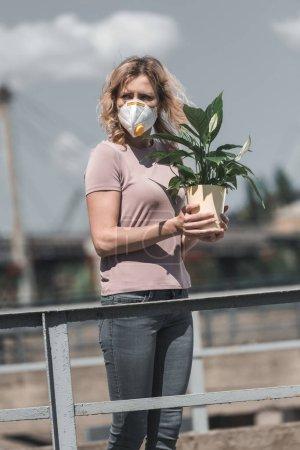 Photo pour Femme au masque de protection tenant une plante en pot verte sur le pont et à la recherche, concept de pollution aérienne - image libre de droit
