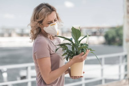 woman in protective mask looking at potted plant on bridge, air pollution concept