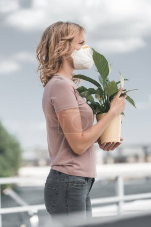 side view of woman in protective mask holding potted plant on bridge, air pollution concept