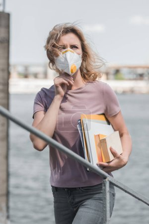 woman in protective mask standing on bridge with books and looking up, air pollution concept