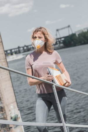 Photo for Woman in protective mask standing on bridge with books, air pollution concept - Royalty Free Image