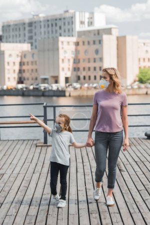 mother and daughter in protective masks holding hands on pier near river, air pollution concept