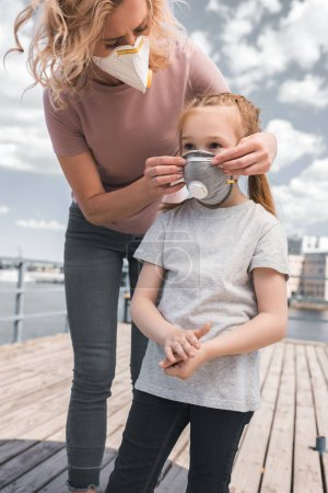 Photo for Mother wearing protective mask on daughter for breathing, air pollution concept - Royalty Free Image