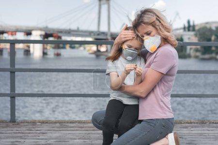mère en fille étreignant masque de protection sur le pont, la notion de pollution aérienne
