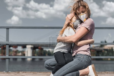 Photo for Mother and daughter in protective masks hugging on bridge, air pollution concept - Royalty Free Image
