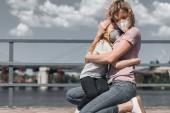 """Постер, картина, фотообои """"мать и дочь в защитных масок, обнимать на мосту, концепция загрязнения воздуха"""""""
