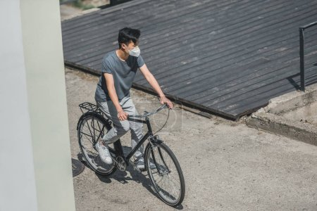 high angle view of asian teen in protective mask riding bicycle in city, air pollution concept
