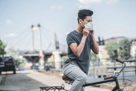 asian teen wearing protective mask with bicycle, air pollution concept