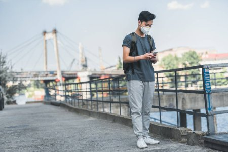 asian teen in protective mask using smartphone, air pollution concept