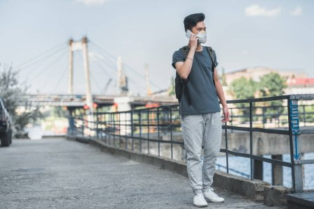 asian teen in protective mask talking by smartphone on bridge, air pollution concept