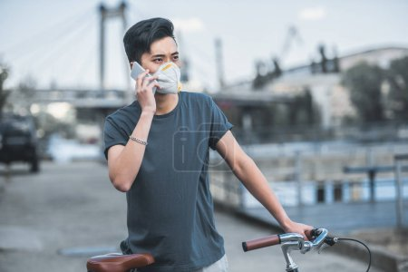asian teen in protective mask talking by smartphone and leaning on bicycle, air pollution concept